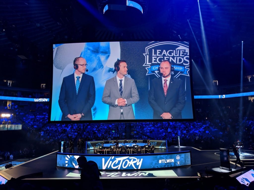 Three announcers on speaking on an arena jumbotron at a LoL event.