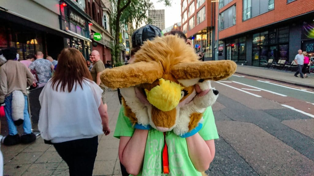 Person dressed in a partial furry costume standing on a sidewalk