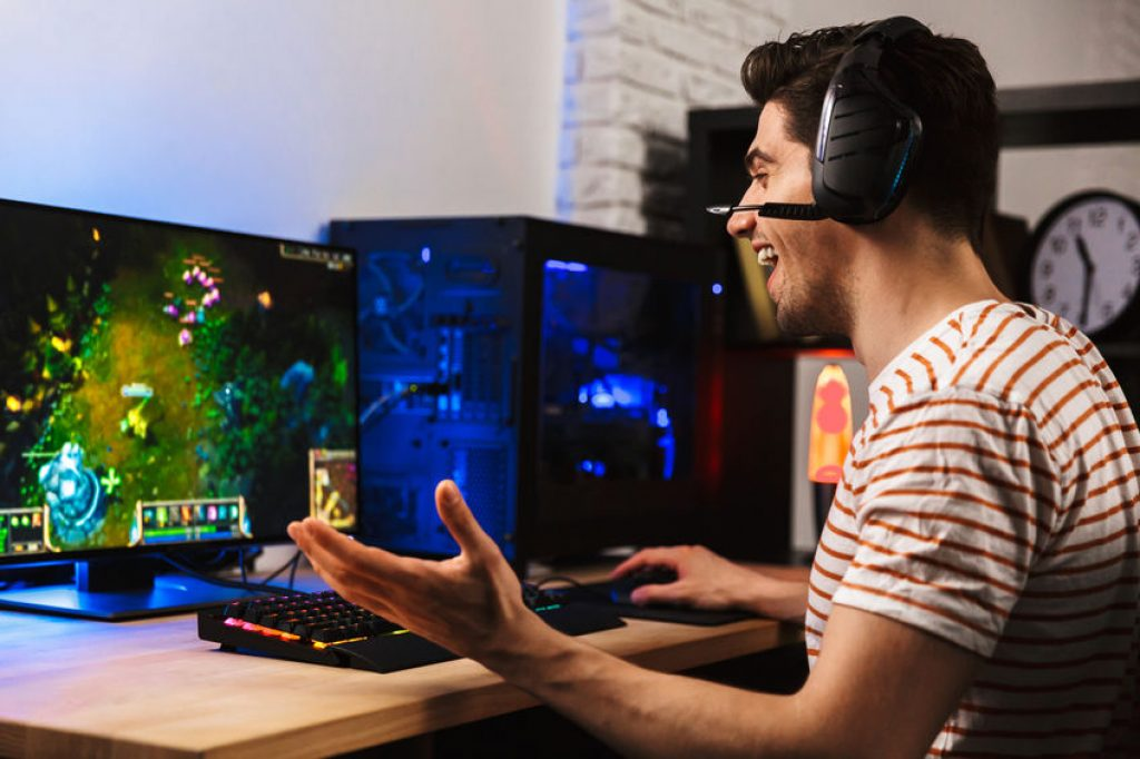 Gamer man playing video games on computer wearing headphones and using backlit colorful keyboard