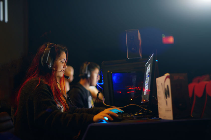Female gamer with headset playing on a gaming pc