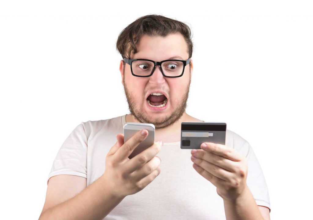man with a shocked look when looking at his credit card