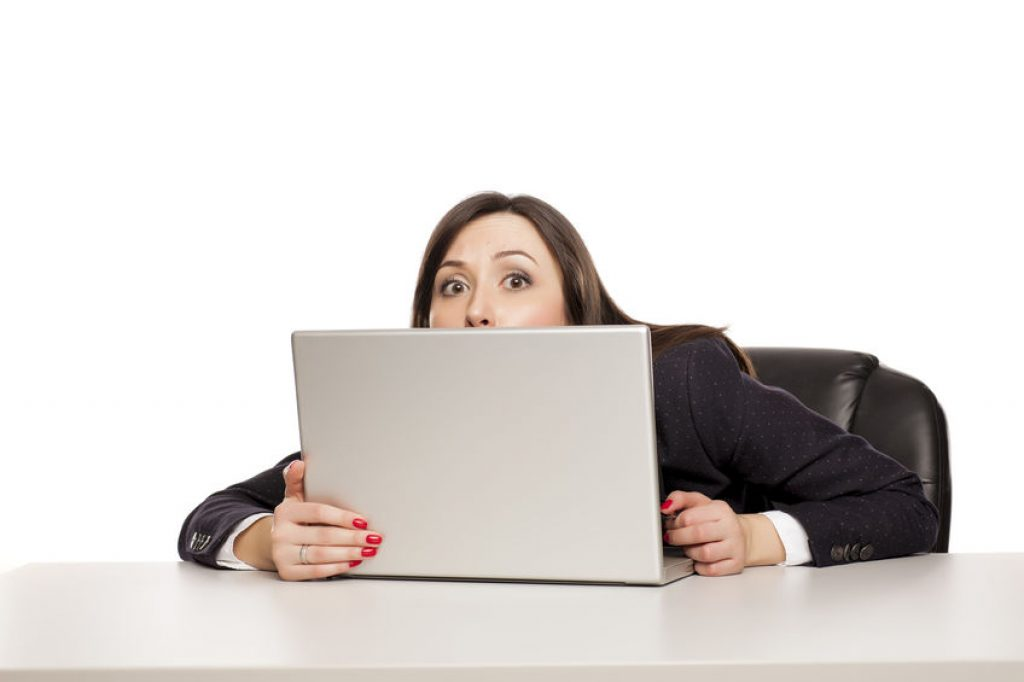 Woman hiding behind her laptop screen